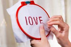 Руки женщин вышивают влюбленности слова Стоковая Фотография