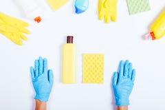Руки женщин в голубой резиновой бутылке перчаток, желтых и зеленых de Стоковое Изображение