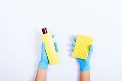 Руки женщин в голубых резиновых перчатках держа желтую бутылку det Стоковые Фотографии RF