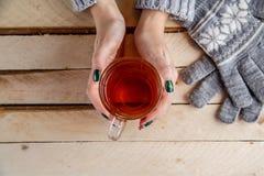 Руки женщин в сером свитере и серых mittens держат прозрачное стекло чая Взгляд сверху на светлой винтажной деревянной предпосылк стоковые фотографии rf