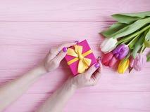 Руки женщин держат красоту праздник подарочной коробки марширует день рождения, представляют букет тюльпанов на розовой деревянно стоковые изображения