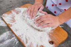 Руки женщин замешивают тесто темной муки рож стоковые изображения rf