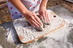 Руки женщин замешивают тесто темной муки рож стоковая фотография rf