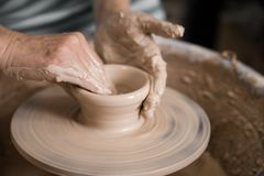 Руки женщин и колесо гончара стоковое изображение