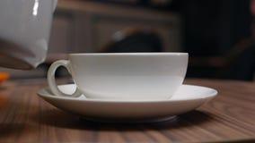 Руки женщин льют чай в белую чашку от чайника в кафе closeup Выпивать чая 4K видеоматериал