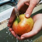Руки женщин моют Яблоко под двигателем воды в раковине Яблоко сочно, чистый Яблоко - красно-желтое Намочите выплеск Стоковое Фото