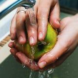 Руки женщин моют Яблоко под двигателем воды в раковине Яблоко сочно, чистый Яблоко - красно-желтое Намочите выплеск Стоковое Изображение RF