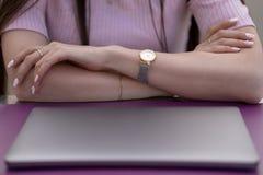 Руки женщин на таблице перед закрытым ноутбуком стоковое изображение rf
