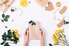 Руки женщин пакуют подарки на белой таблице Стоковое Изображение