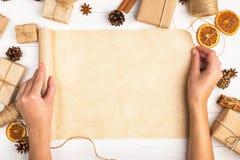 Руки женщин поворачивают крен бумаги ремесла На фоне высушенного апельсина, циннамон, конусы сосны, анисовка на белые животики стоковое изображение rf