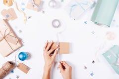 Руки женщин подготавливают подарки и украшения Стоковая Фотография