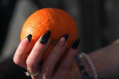 Руки женщин с искусствами ногтя на ногтях держа оранжевый плод стоковое фото rf
