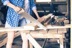 Руки женщин с концом-вверх пилы увидели доску, девушка приниманнсяое за плотничество стоковое фото rf