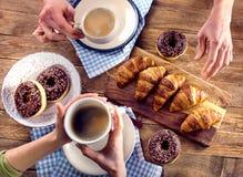 Руки завтрака держа чашки кофе и круассаны Стоковые Изображения