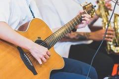Руки играя акустическую гитару, конец вверх стоковая фотография