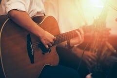Руки играя акустическую гитару на этапе, конец вверх стоковые изображения
