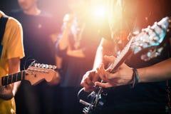 Руки играя гитару на этапе, конец вверх стоковые фотографии rf