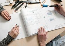 Руки дизайнеров рисуя взгляд сверху схемы Стоковые Фото