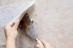 Руки извлекая старые обои с помощью шпателю во время t Стоковые Изображения RF
