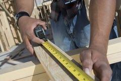 Руки измеряя деревянный луч стоковое изображение
