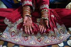 2 руки индийской невесты с mehndi хны и bangles и красным платьем свадьбы стоковая фотография rf