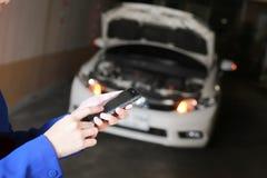 Руки используя smartphone вызывают аварийную ситуацию автомобиля сломленный автомобиль стоковые изображения rf