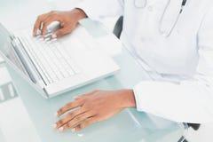 Руки используя компьтер-книжку на медицинском офисе Стоковые Изображения RF