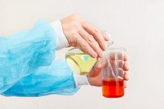 Руки исследователя делая химические эксперименты в лаборатории Стоковые Изображения