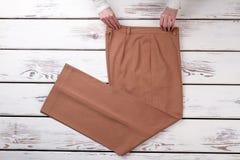 Руки и брюки на деревянной предпосылке стоковые фотографии rf