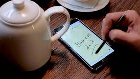 Руки и грифель используя таблетку компьютера Вы можете сделать его на экране сток-видео
