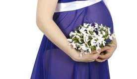 Руки и живот беременной женщины в голубых одеждах стоковое изображение