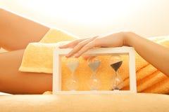 Руки и ноги в салоне спы с sandglass Стоковое фото RF