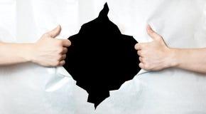 Руки и отверстие в бумаге Стоковые Фотографии RF