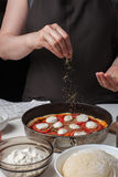 Руки кашевара женщины брызгают итальянское сырцовое oreano маргариты пиццы на темной предпосылке На белой лож таблицы ингридиенты Стоковое фото RF