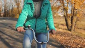 Руки колеса девушки изогнутого владением велосипеда Маленькая девочка управляет велосипедом на дороге в парке осени видеоматериал