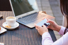 Руки коммерсантки с компьтер-книжкой и мобильным телефоном во время завтрака. Стоковая Фотография
