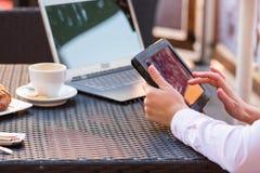 Руки коммерсантки с компьтер-книжкой и мобильным телефоном во время завтрака. Стоковые Изображения