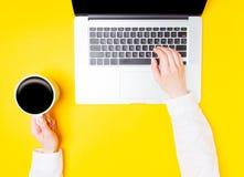 Руки коммерсантки с компьтер-книжкой и чашкой кофе Стоковое Изображение