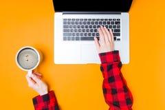 Руки коммерсантки с компьтер-книжкой и чашкой кофе Стоковая Фотография