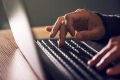Руки компьютерного программиста и хакера печатая клавиатуру компьтер-книжки