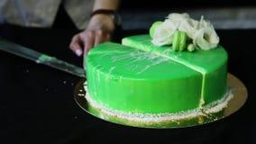 Руки кондитера отрезали вниз с зеленого торта в части видеоматериал