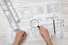 Руки конца-вверх архитектора пока работающ процесс с лупой Стоковые Фотографии RF