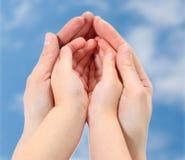 Руки конца-вверх матери и младенца на небе Стоковые Изображения RF