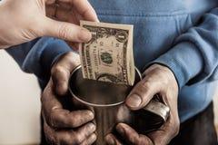 Руки конца-вверх с руками чашки пакостными человека попрошайки бездомного и долларовой банкноты милостынь Стоковые Фото