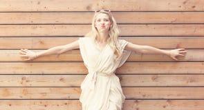 Руки красивой молодой белокурой женщины стоящие распространили на стене предпосылки деревянных планок Тонизированный в теплых цве Стоковое Фото