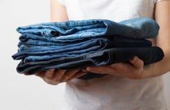 Руки крупного плана кавказские женские держа 3 пары голубых джинсов джинсовой ткани белизна изолированная предпосылкой стоковое изображение