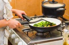 Руки крупного плана женщины жаря овощи на плите кухни, варя концепцию Стоковое фото RF