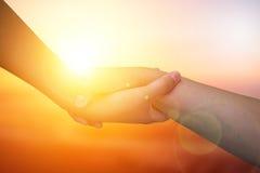 Руки крупного плана используемые для того чтобы помочь одину другого на предпосылке против как крюка hang долларов принципиальной Стоковые Фото