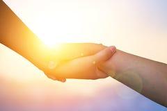 Руки крупного плана используемые для того чтобы помочь одину другого на предпосылке против как крюка hang долларов принципиальной Стоковое Изображение