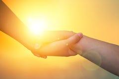 Руки крупного плана используемые для того чтобы помочь одину другого на предпосылке против как крюка hang долларов принципиальной Стоковая Фотография RF